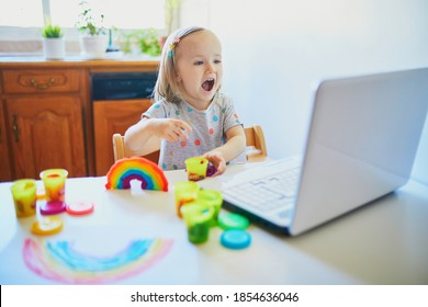 Toddler girl playing modelling clay in front of laptop. Kid using computer to communicate with friends or kindergartners. Education or online communication for kids. Stay at home entertainment