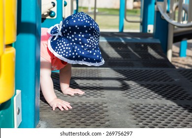 Toddler girl playing on tot lot on Spring day.