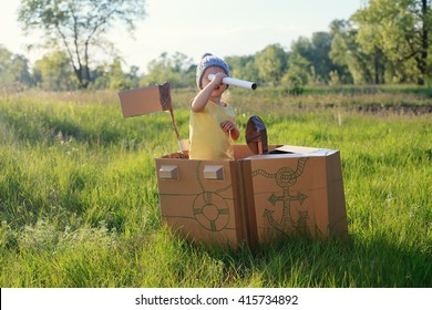toddler girl playing with paperboard ship