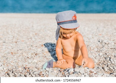 Toddler girl playing with pebbles on beach - Cirali, Antalya Province, Turkey