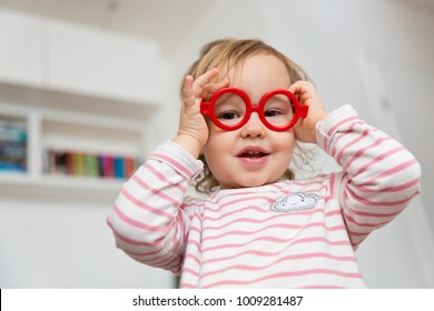 Toddler girl playing with plastic glasses