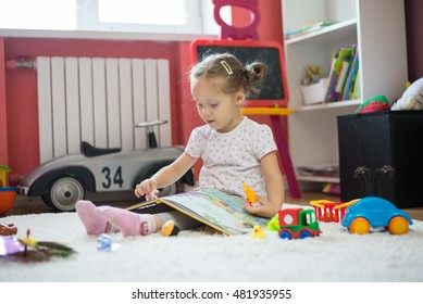 toddler girl playing and reading in the children room
