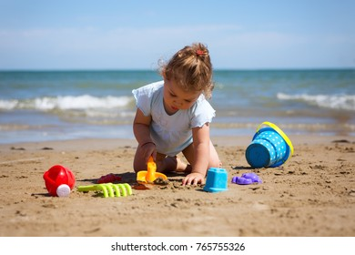 Toddler girl playing in the sand at the beach.