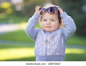 Toddler Girl Playing with Sunglasses