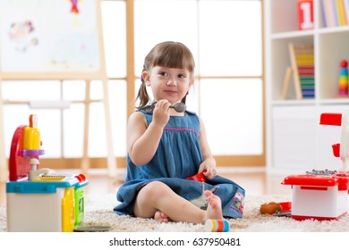toddler girl playing toy kitchen at home