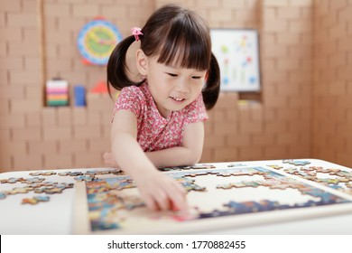 toddler girl playing wooden puzzle at home