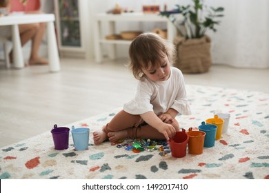 Toddler girl plays with beads and multicolored buckets, the development of fine motor skills and sensory development, the study of colors. Self-study of the child and Montessori method