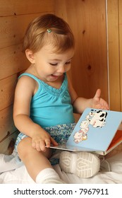 toddler girl reading a board book