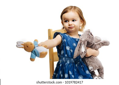toddler girl sharing and offering a plush toy rabbit