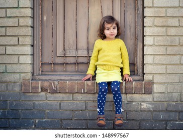 Toddler Girl Sitting by an Old Building
