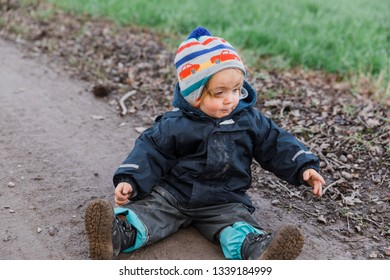 Toddler girl sitting with muddy pants on dirt road – Kempen, Germany