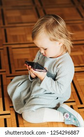 Toddler girl sitting on the floor and watching video on smartphone