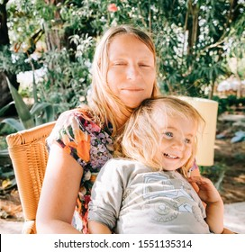 Toddler girl sitting on grandmother's lap - Cirali, Antalya Province, Turkey