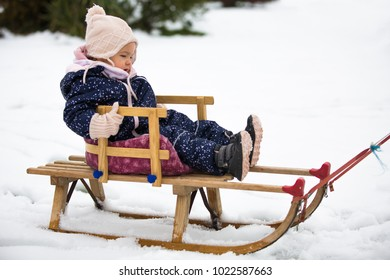 Toddler girl sitting on the sled in the snow, wearing wool gloves and hat and a blue winter suit