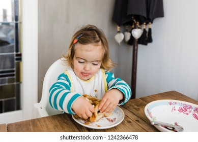 Toddler girl sitting on table and playing with food -  Hindeloopen, Netherlands