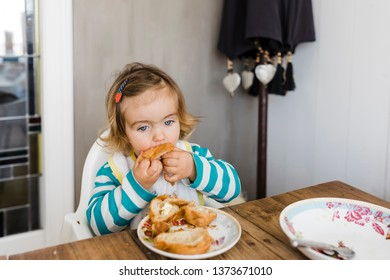 Toddler girl sitting on table and eating -  Hindeloopen, Netherlands