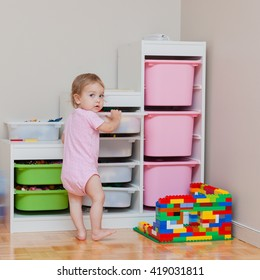 Toddler girl standing near toys sorting system. Toys arrangement in room: safety, easy and comfortable.