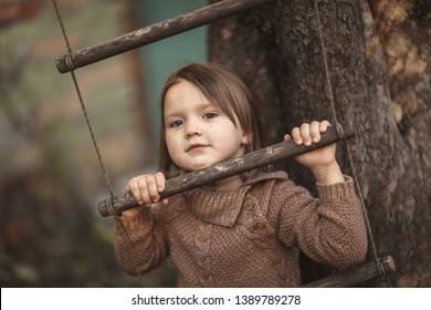Toddler girl swinging on the rope ladder, happy childhood and chocolate toning, lifestyle