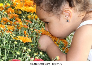 A toddler girl taking time to smell the flowers