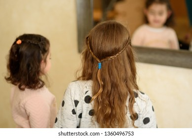 Toddler girl and teenager girl play in room looking at themselves in a mirror.