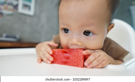 Toddler girl try to eating watermelon on the table.