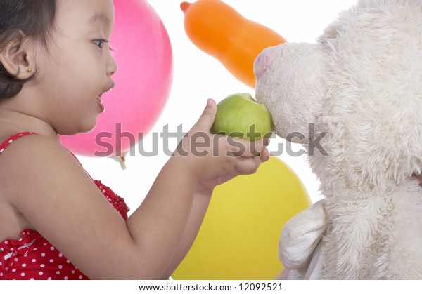 toddler girl trying to feed teddy bear