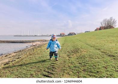 Toddler girl walking on dyke – Hindeloopen, Netherlands, Europe