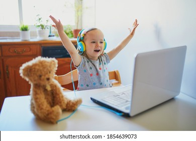 Toddler girl wearing eraphones with laptop. Kid using computer to communicate with friends, elderly relatives or kindergartners. Education or online communication for kids. Stay at home entertainment
