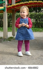 Toddler girl wearing jeans dress playing with sand in backyard