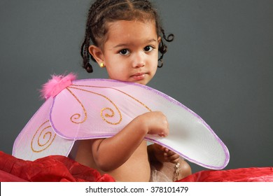 toddler girl wearing pink butterfly wings