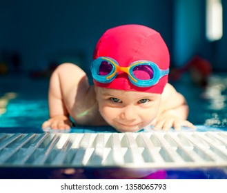 Toddler girl wearing red swimsuit leaning at the edge of a swimming pool while learning to swim, focus on goggles