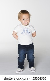 A toddler girl in white t-shirt and blue jeans standing with hands behind back on white background
