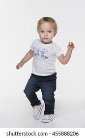 A toddler girl in white t-shirt and blue jeans walking with a cookie in her hand on white background
