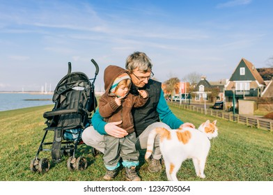 Toddler with grandfather and cat on dyke – Hindeloopen, Netherlands, Europe