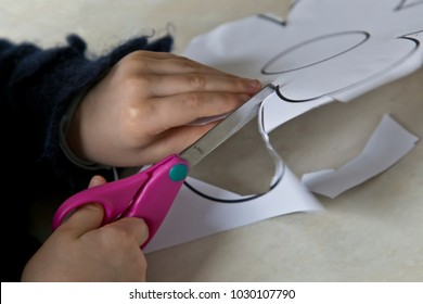 Toddler hands cutting a paper flower with pink scissors. Cutting activities for scissor skills at home or at school.