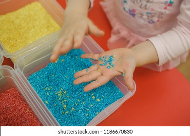 Toddler hands playing with rainbow rice in the sensory box. Baby's sensory educational kit