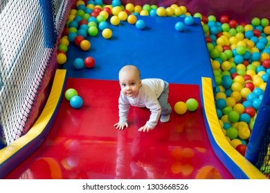 Toddler having fun in ball pit in kids amusement park and indoor play center. Child playing with colorful balls in playground ball pool. Activity toys for little kid