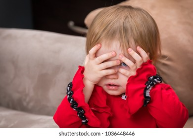 A toddler with her hands over her eyes