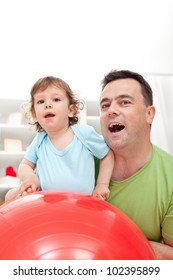 Toddler and his father playing with gymnastic ball - closeup
