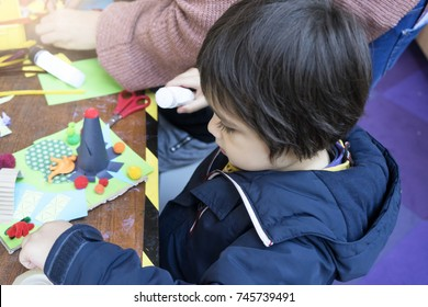 Toddler holding colored paper and glue on paper plate in kindergarten, The teacher teaching school kids, Creative preschool children with teacher,little boy making image with paper