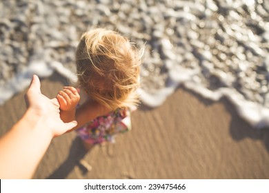Toddler holding parent's hand at the beach