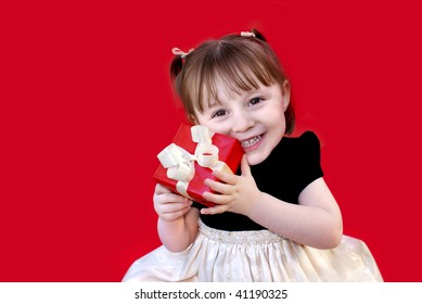 Toddler holds a red gift.