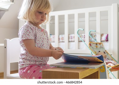 Toddler at home smiling and reading a book