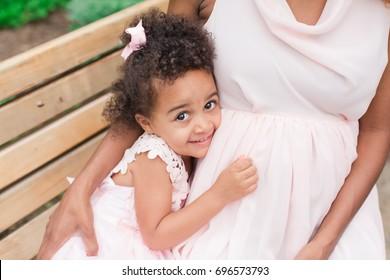 Toddler hugging pregnant mother