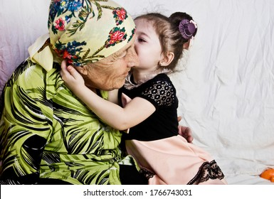 Toddler hugs his old grandmother. A child kisses the wrinkles of an old grandmother. A small child kisses his grandmother. Happy grandmother with a small child play fun. With family.