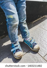 Toddler in jeans draws with crayons on the asphalt in sunny day. Kid's jeans and sneakers are covered with colorful stains. Outdoor leisure activity.