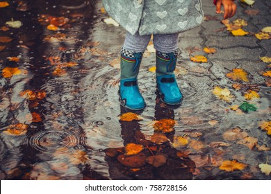 Toddler jumping in pool of water at the autumn day.