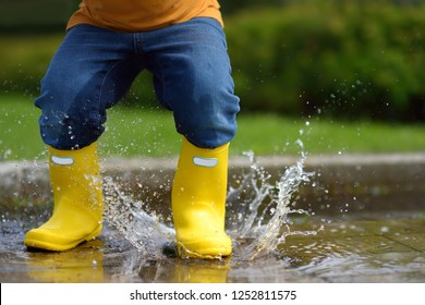 Toddler jumping in pool of water at the summer or autumn day. Outdoors activity for kids.
