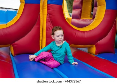Toddler kid stopped to contemplate in the middle of a game of bounce on the trampoline