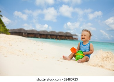 Toddler laughing sitting with toys and playing with sand
